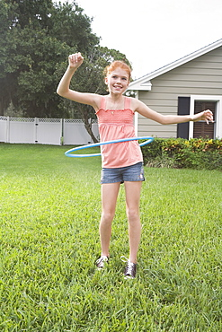 Girl hula hooping in backyard