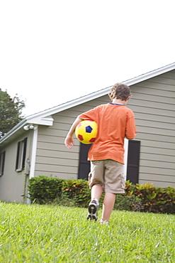 Boy carrying soccer ball in backyard