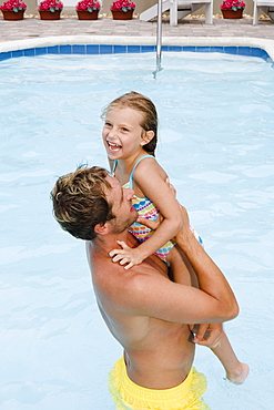 Father lifting daughter out of swimming pool