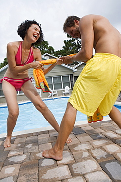 Couple playing tug-of-war with towel