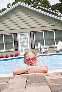 Girl leaning on edge of swimming pool