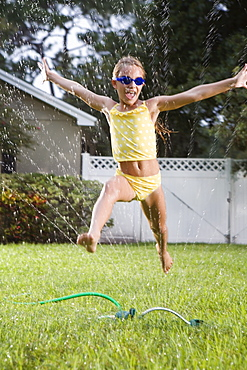 Girl running through sprinkler