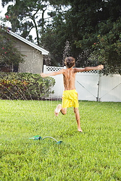 Boy running through sprinklers