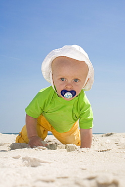Baby boy crawling on beach