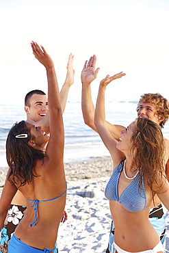 Young friends high fiving on beach