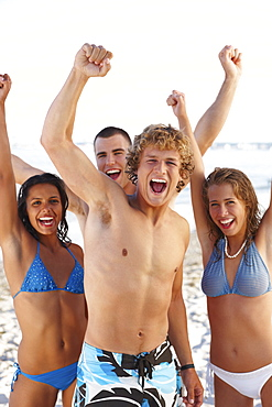 Young friends raising arms on beach
