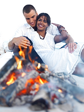 Young couple hugging by campfire on beach
