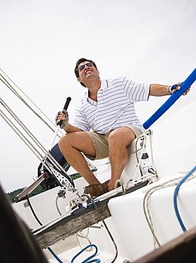 Man steering sailboat
