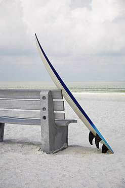 Surfboard leaning against bench