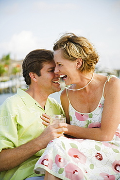 Woman laughing while husband bites necklace