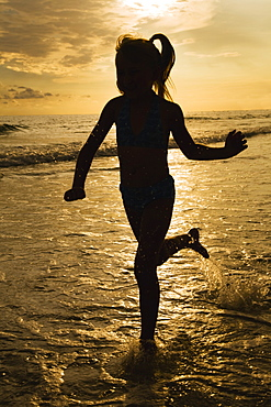 Girl running in ocean surf at sunset, Florida, United States