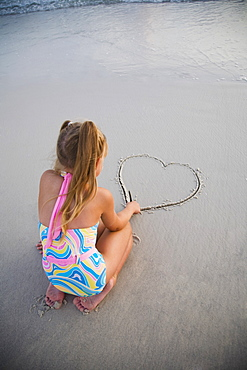 Girl drawing heart in sand, Florida, United States