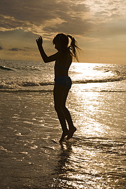 Girl in ocean surf at sunset, Florida, United States