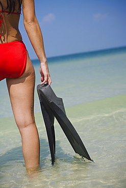Rear view of woman holding flippers, Florida, United States