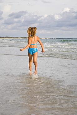 Girl running in ocean surf, Florida, United States
