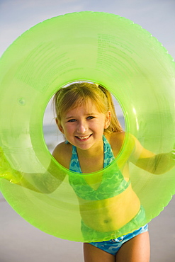 Girl looking through middle of inner tube, Florida, United States