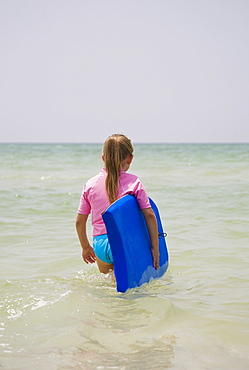 Young girl walking into water with boogie board, Florida, United States