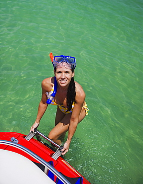 Woman in snorkeling gear climbing off boat, Florida, United States