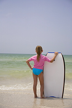 Young girl holding boogie board, Florida, United States