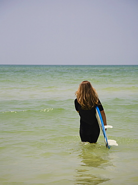 Girl walking into water with surfboard, Florida, United States