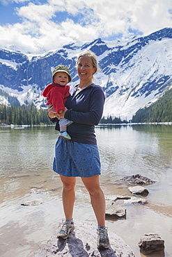 Woman with son (4-5) standing on lakeshore, Avalanche Lake, Glacier National Park, Montana, USA