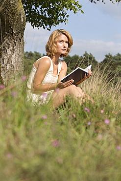 Woman sitting on grass and reading book, Netherlands, Gelderland, Hatertse Vennen