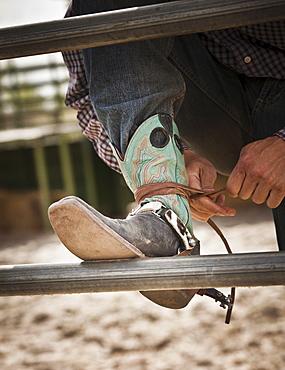 Close-up of cowboy tying shoe