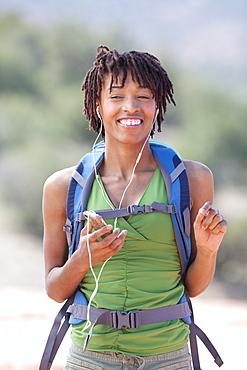Smiling female hiker listening music