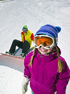Daughter (10-11) posing with father sitting on ground with snowboard in background