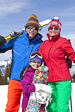 Grandparents with girl (10-11) posing during ski holiday