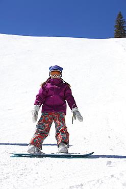 Girl (10-11) snowboarding
