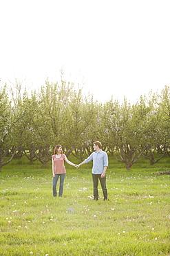 USA, Utah, Provo, Young couple walking through orchard