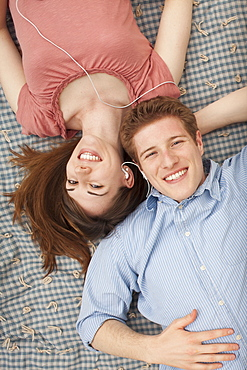 Young couple with mp3 player lying on blanket