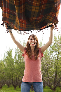 Young woman holding blanket in orchard