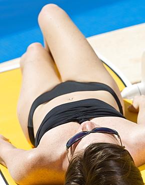 Spain, Costa Blanca, Woman sunbathing on poolside