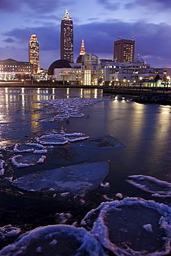 USA, Ohio, Cleveland skyline across frozen lake at sunrise