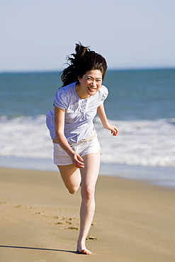 USA, California, Point Reyes, Young woman running on beach