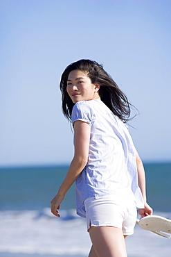 USA, California, Point Reyes, Young woman walking near sea