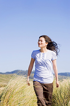 USA, California, Point Reyes, Young woman walking in grass
