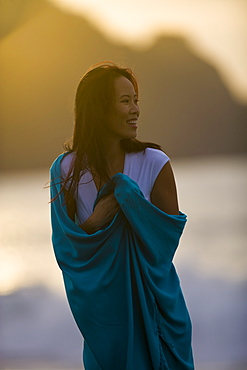 USA, California, San Francisco, Young woman wrapped in blanket at coast