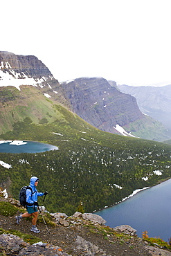 USA, Montana, Glacier National Park, Mid adult woman hiking with backpack during rain