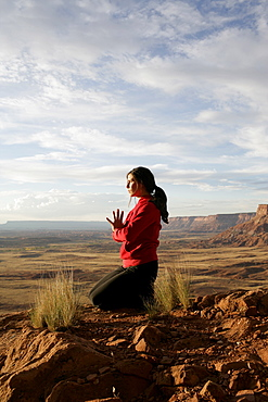 USA, Utah, Canyonlands National Park, woman meditating on rock