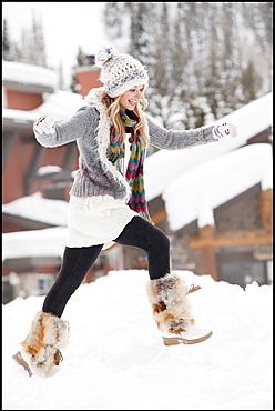 USA, Utah, Salt Lake City, young woman walking through snow in resort
