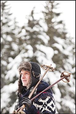 USA, Utah, Salt Lake City, man carrying ski poles