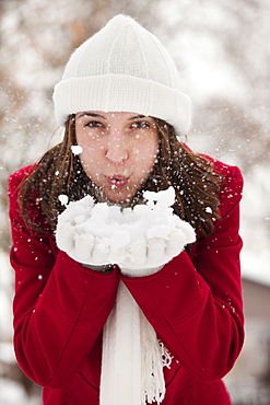 USA, Utah, Lehi, Portrait of young woman blowing snow