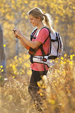USA, Utah, young woman taking photograph in forest