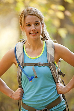 USA, Utah, young woman with backpack in forest