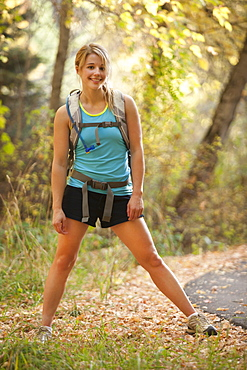 USA, Utah, young woman standing by footpath in forest