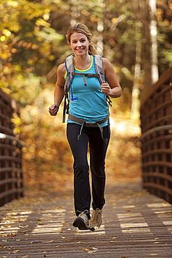 USA, Utah, young woman jogging on footbridge