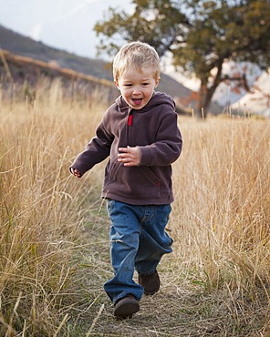 Boy running in meadow